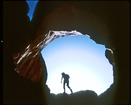 Sillouetted hiker under Double Arch
